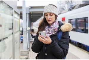 Žena na vlakovém nádraží držící mobil ©EC Audiovisual Service